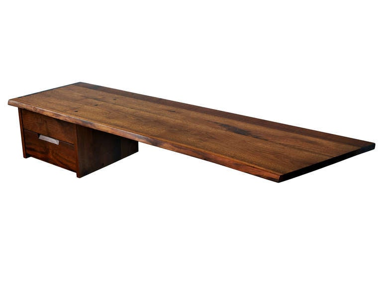 A chic and versatile George Nakashima studio piece, ideal as a space-efficient desk, but equally suited for use as a console. The pure quality of Nakashima's joinery is, as always, a delight to behold; the two drawers are made with astonishing