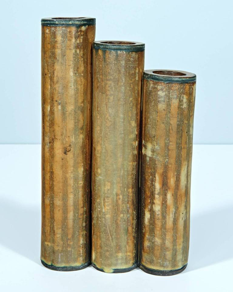 What appear to be organ pipes of ascending height are each perforated by a Gothic arch, openings which allow a view of the stems of the flowers held within. Fully signed.