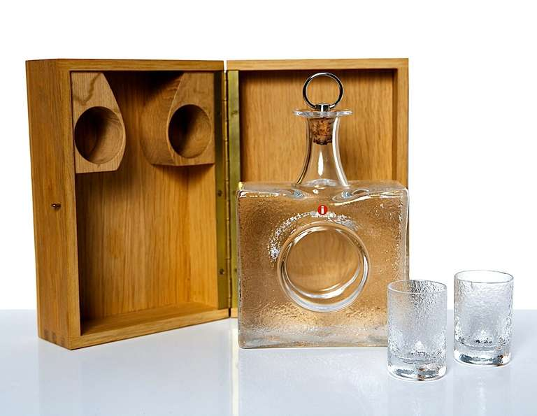 A lovely decanter, carefully boxed with a pair of small glasses, made by Iitala from 1966 until 1973. The high quality of the fitted box makes this set a fine gift. In as-new condition. The 40 cl decanter is signed