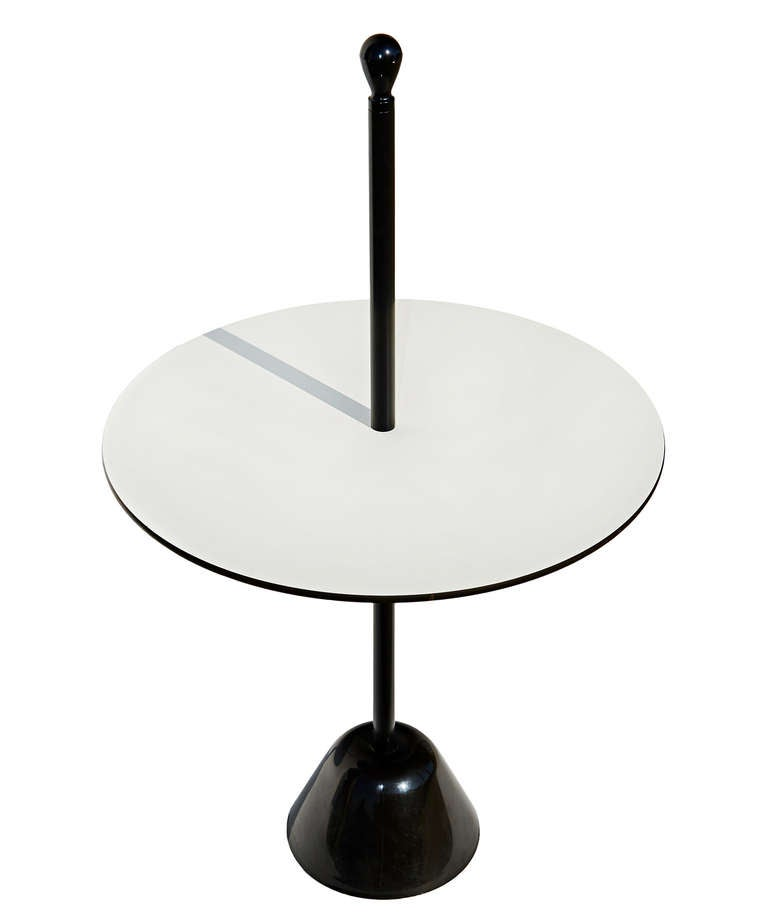 This 1974 service table by Italian design legend Achille Castiglioni has a central black-enameled stem that serves as a useful carrying handle. Made by the equally legendary Italian company, Zanotta.  The table's top measures 19.7 inches in