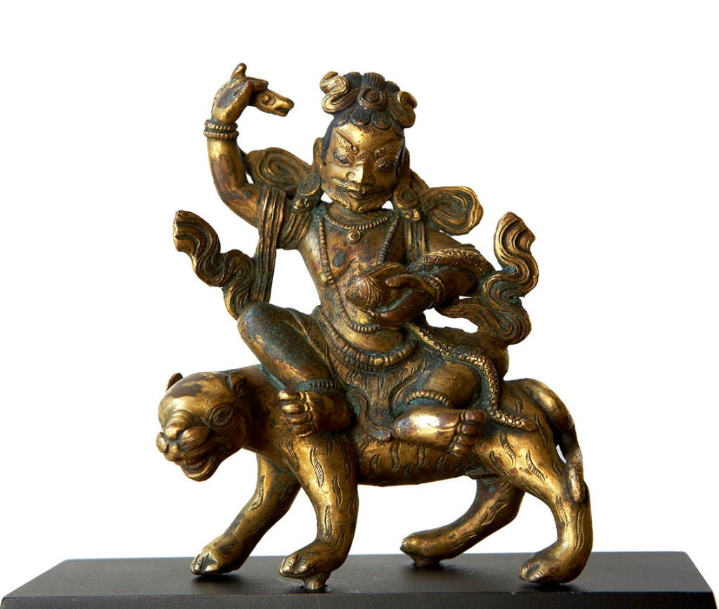 An early and very fine gilt bronze representation of Dombi-Heruka, one of 84 Mahasiddhas (great beings) held in reverence by Tibetan Buddhists. Mahasiddhas were believed to have been actual historical personnages who performed great mystical feats,