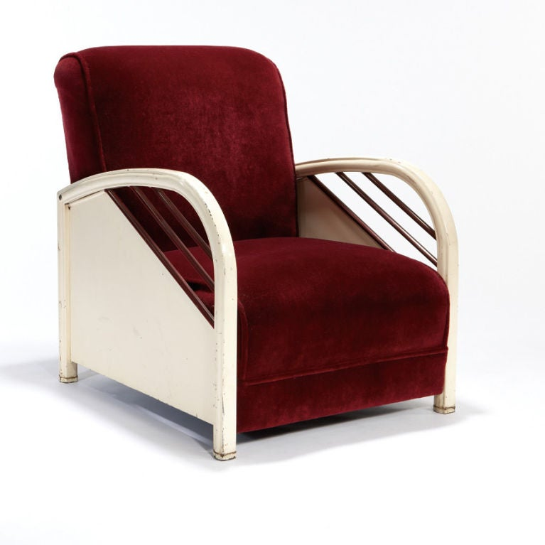 A characterful club chair made of enameled steel, with velvet upholstery, in the streamline Modern style. Attributed to the seminal American industrial designer Norman Bel Geddes, whose obsession with aerodynamics is manifested even in his designs