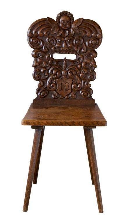 This is a particularly elaborate example of a traditional Swiss chair. It was made in the 19th century in the Alpenzell region of Switzerland, and features beautiful carving in a baroque idiom: stylized faces blowing wind in opposite directions on