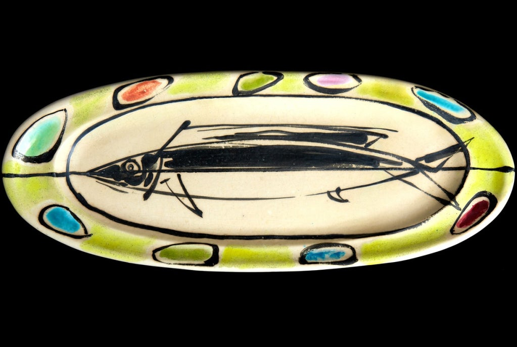 Made to be displayed as a wall-hung plaque, this large Georges Jouve piece would serve admirably as a charger or even a serving dish. Decorated in a marvelously spontaneous hand, with a stylized fish in black against a cream background, surrounded
