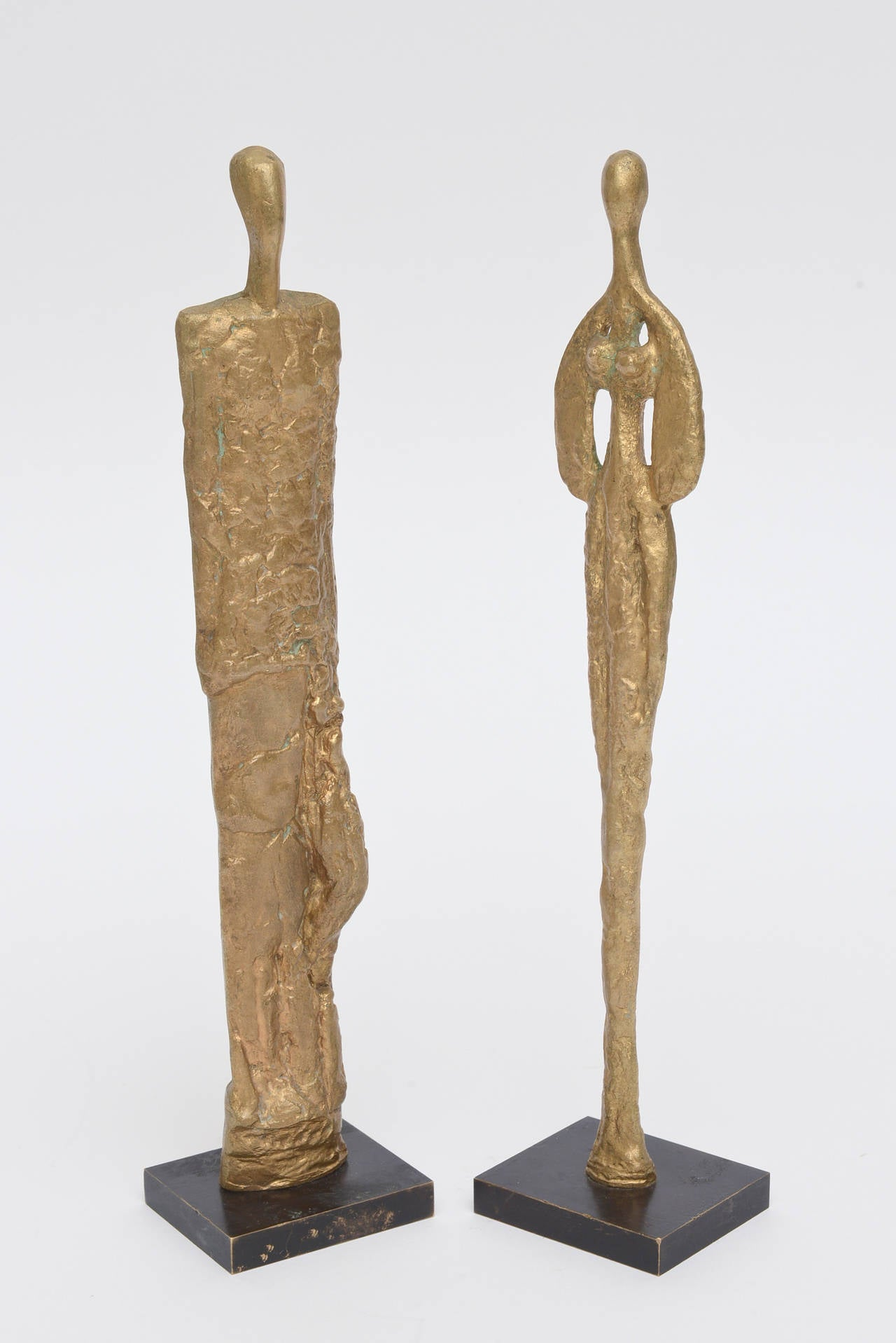 These amazing pair of bronze sculptures of male or female forms are so very much in the style of Giacometti. They are molten bronze and are European. The small square bases are also bronze. The color of the bronze is a rich golden color with texture