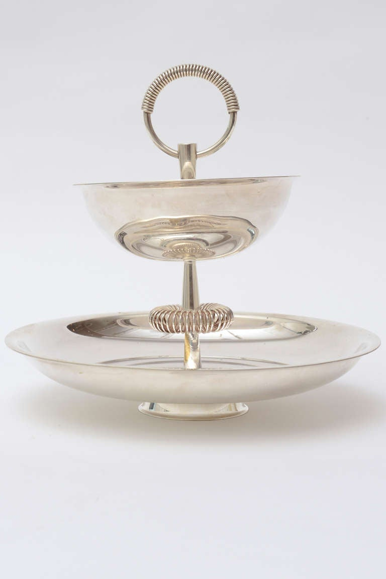 This lovely newly polished Mid-Century Modern silver plate two-tiered serving piece has the wonderful look and style of Tommi Parzinger. The coiled rings on the top and mid portion add dimension and texture. This bowl or serving piece is elegant and