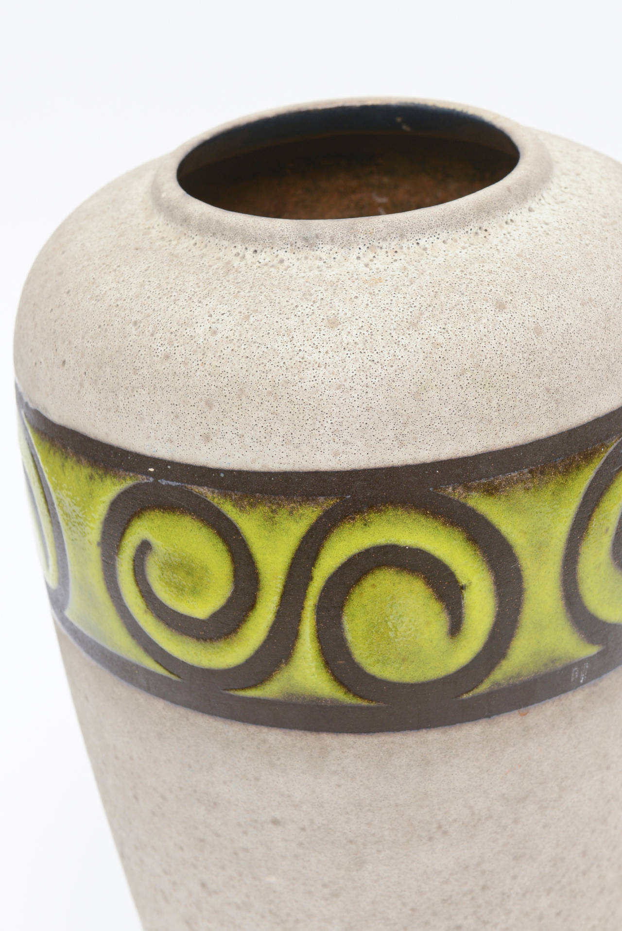 The stunning earthy colors of the grey rough ceramic with the band of the chartreuse glazed polished band with scroll detail adds to the great juxtaposition between earthy and design. There is a partial label on it that reads Eu JA and the number