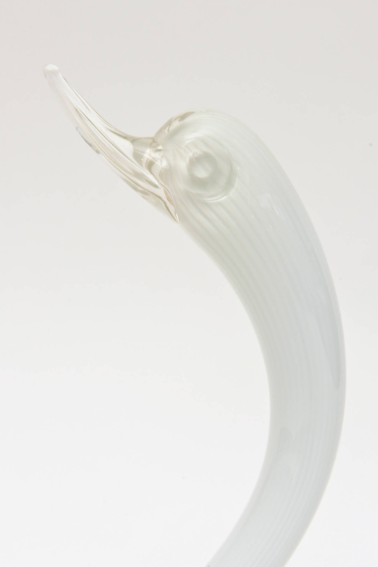 This lovely and graceful Italian Murano Seguso glass swan is white triple cased; white with clear on the outside. The lines of the feathers are abundant throughout. The beak is clear. It is signed but not legible. It is a beauty! It is attributed to