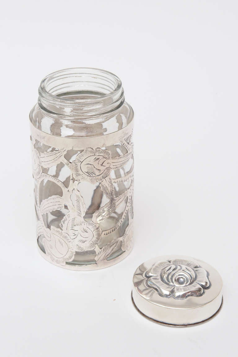The sterling silver design overlay over the clear glass makes this container perfect for serving or many uses. This could be used for serving jam. Would be fabulous in a bathroom setting! Beautiful floral design all hallmarked on the bottom Mexican