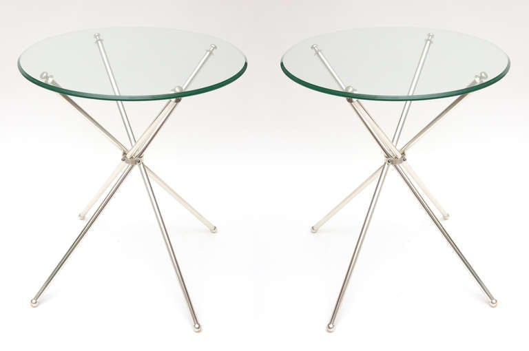 These pair of vintage silver plate tripod side tables are elegant and unusual. These tripod tables actually fold up. The legs have little balls on the bottom. The glass rests on also ball posts of a different shape. The diameter of the glass is 20