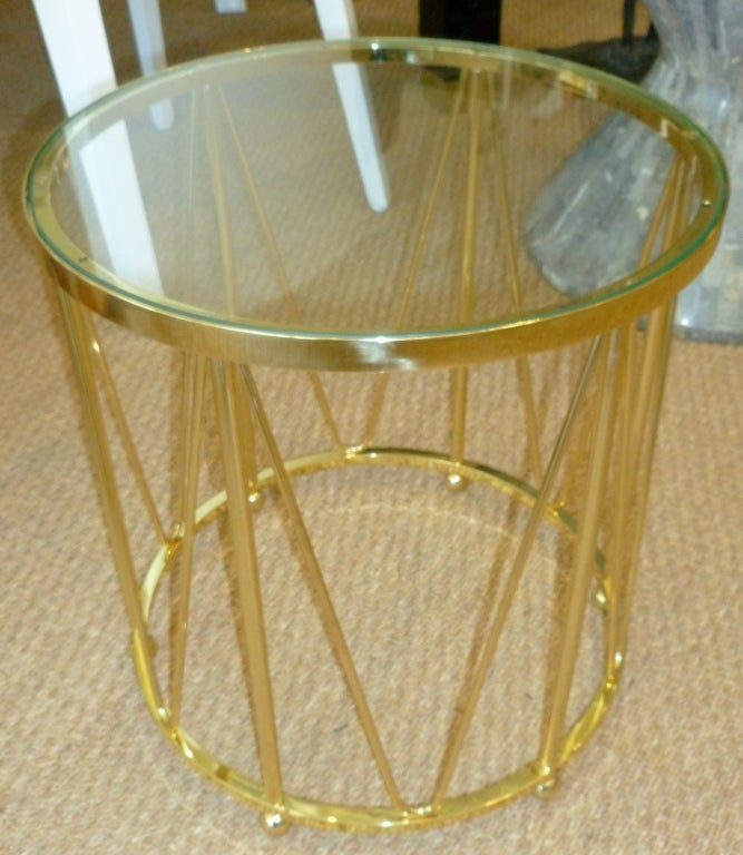 The greatness of this polished brass vintage drum table is that it stands alone as a side and or end table. It has good weight to it and a fabulous look, very sculptural and timeless. The top is glass. There is only one of these and perfect between