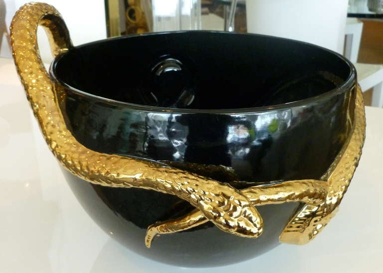 Glazed black and gold ceramic serpent bowl centerpiece at