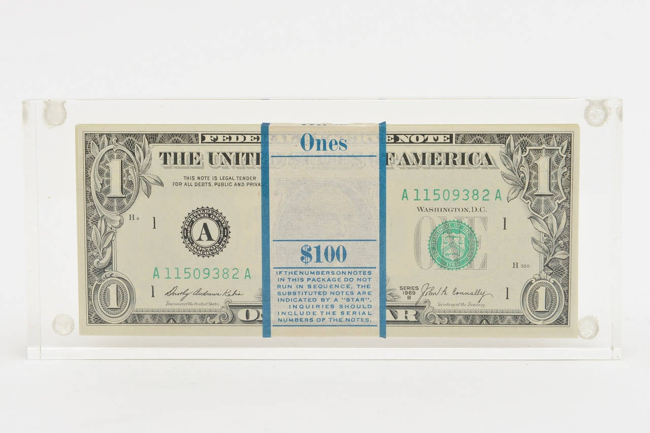 Two real dollar bills are on the front and back in this vintage allusion dollar bill Lucite sculpture. What is in the middle is a mystery. Are they real dollar bills in the center banded together to look real.  They may be real. That is the dollar