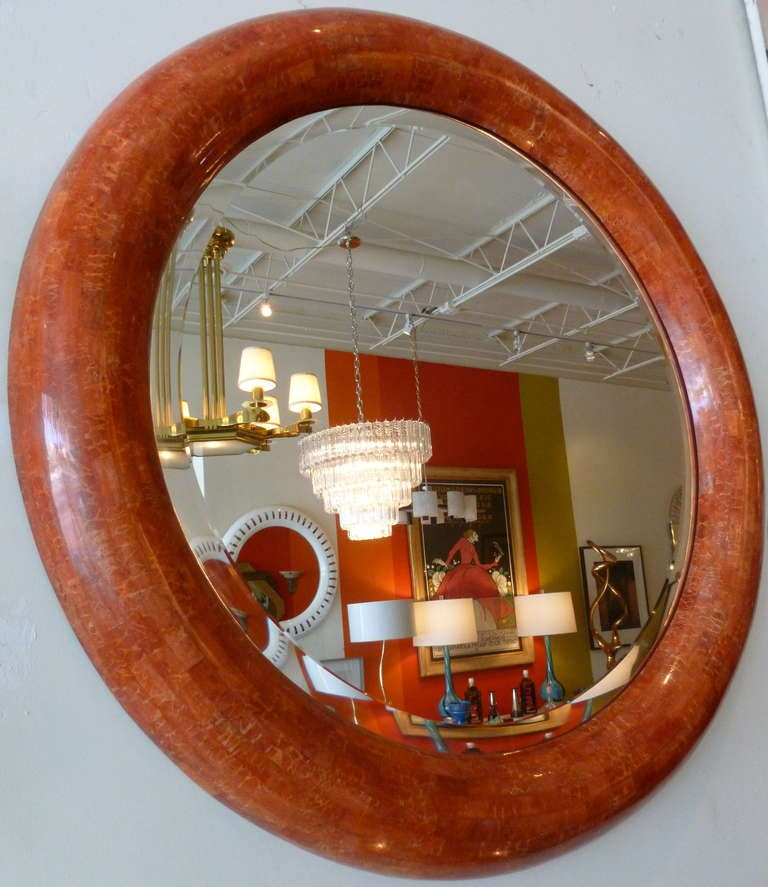 The layering of luscious colors or orange red to coral make up this round thick tessellated stone beveled mirror. The stone resembles veining. This is in the style of Karl Springer and Maitland-Smith. The interior diameter of the beveled mirrors