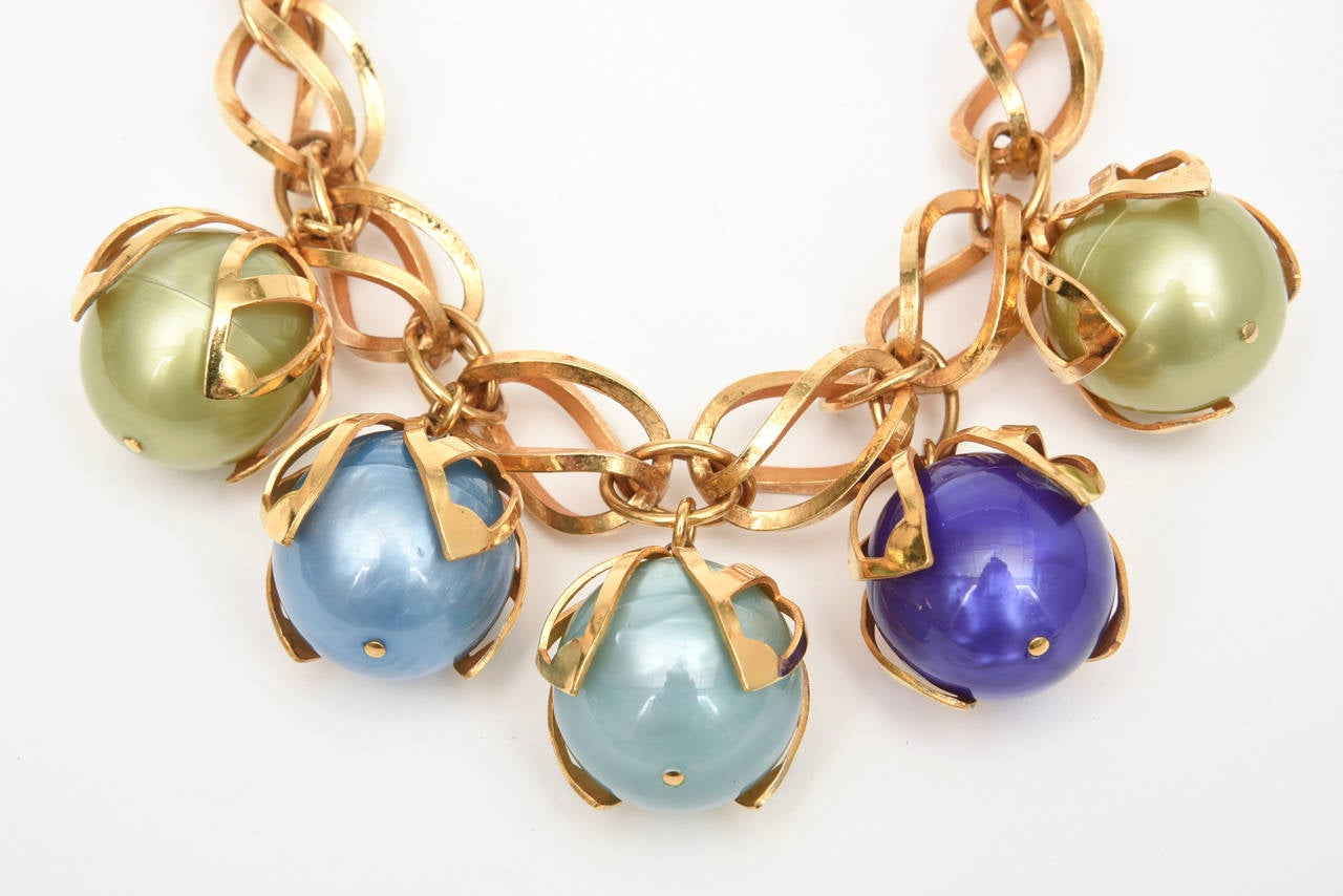 This theatrical and statement French necklace by Dominique Aurientis has 4 large balls of resin that are caged in with the gold washed metal that are attached to the twisted link necklace . The 4 large balls in luscious colors of unusual blues and