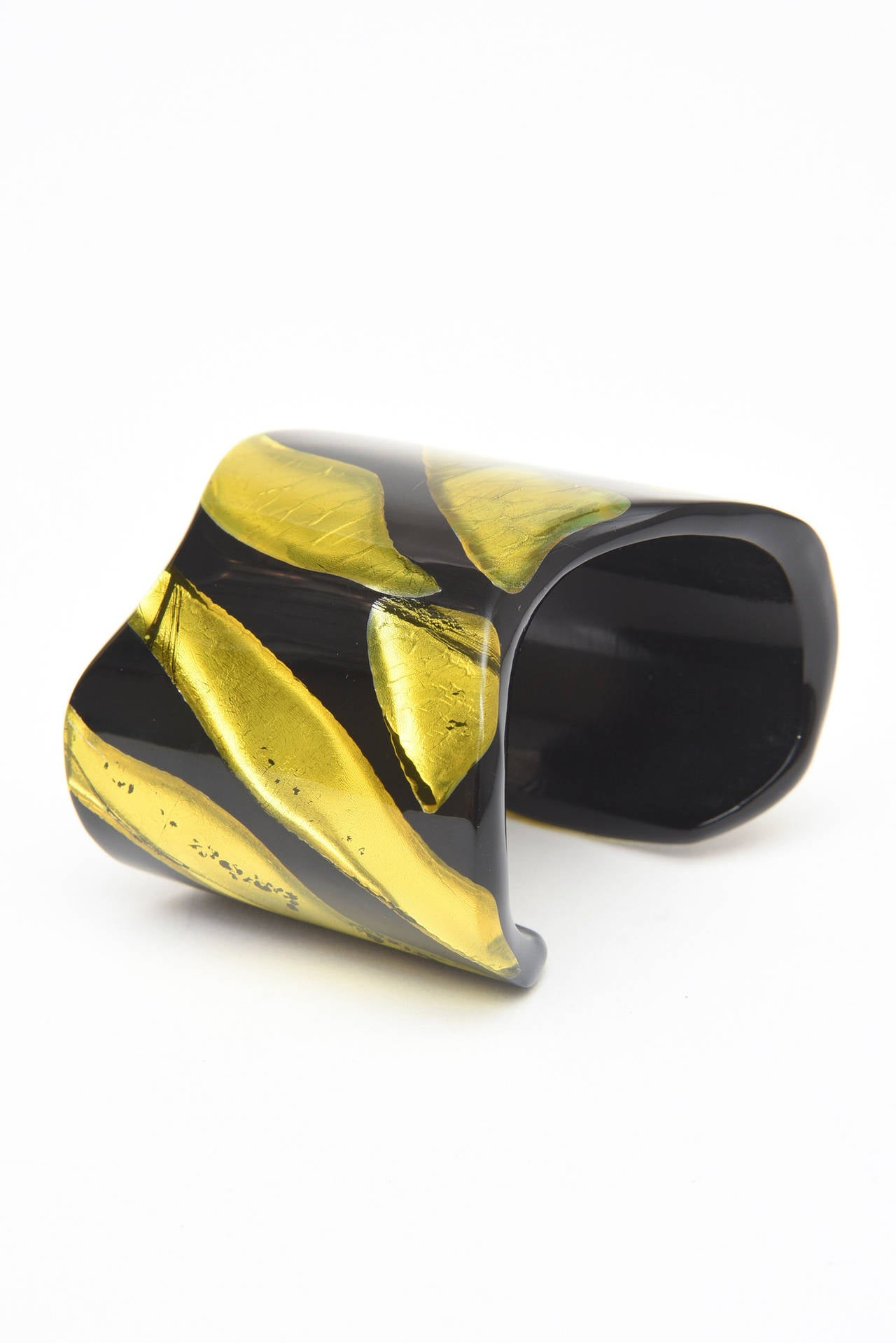 The juxtaposition of embedded chartreuse resin that looks like foil against black plexiglass becomes almost 3 dimensional. This sculptural one of a kind cuff is signed Vigneri 1984 copyright.  It is Italian and has the shape of the sterling bone