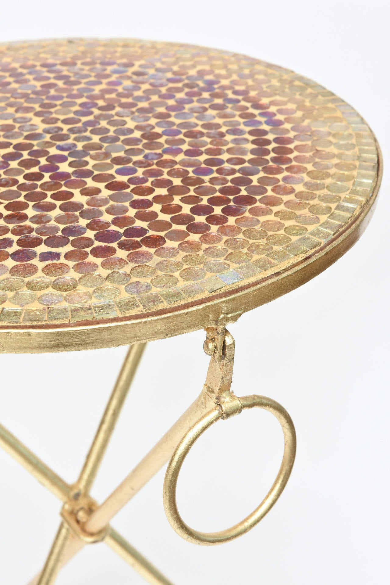 These lovely Italian tripod side tables are from the 1960s. They are real gold leaf over iron and have beautiful original glass mosaic tops that almost have an iridescence to them. Each table has one gold ring on one side. The ball feet have