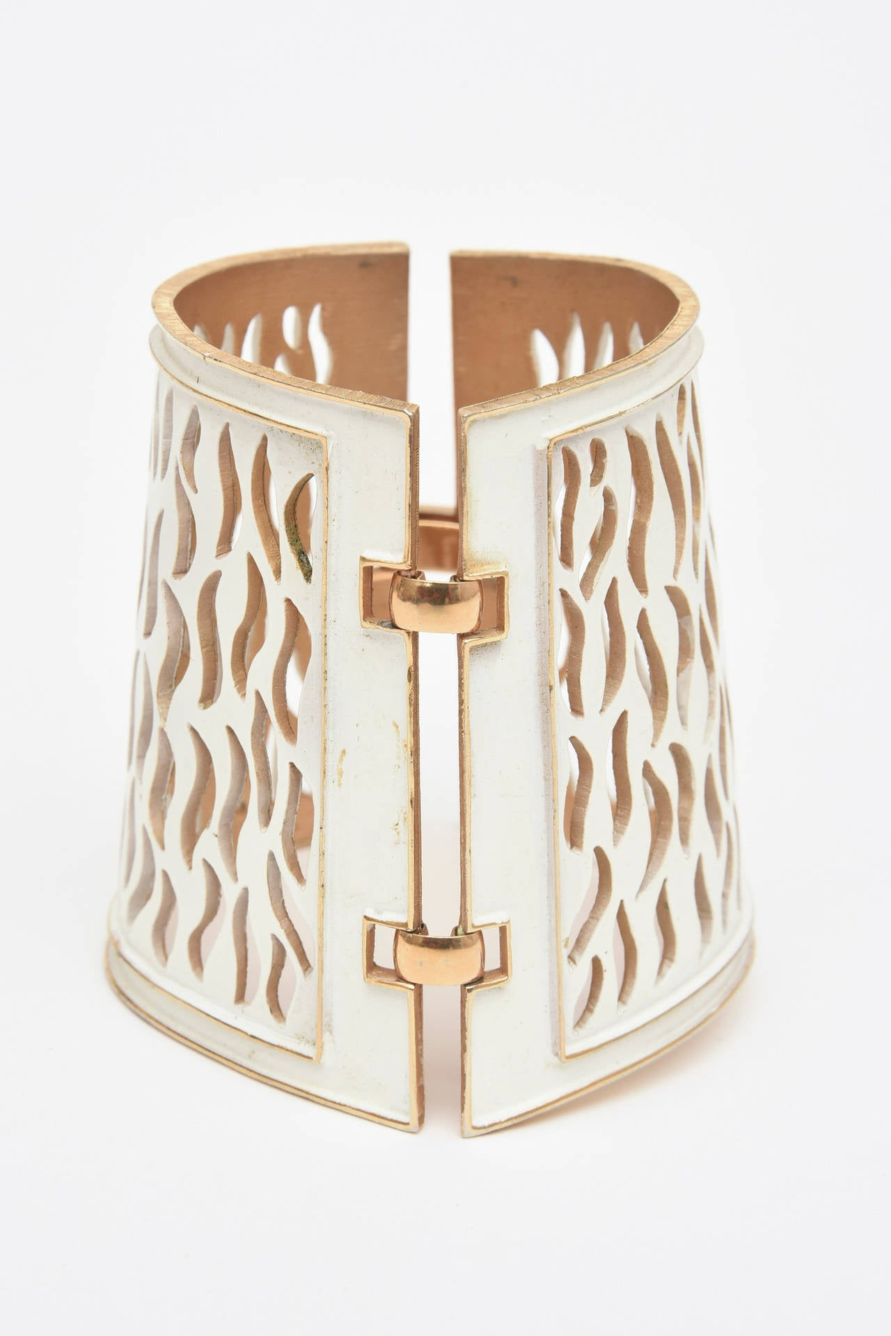 This wonderful Trifari sculptural cuff is fun and conversational. The off white enamel is beautiful against the gold. The cutout details are artistic. The sculptural cutouts are like laser cut enemale. It has a gold latch and is connected with he