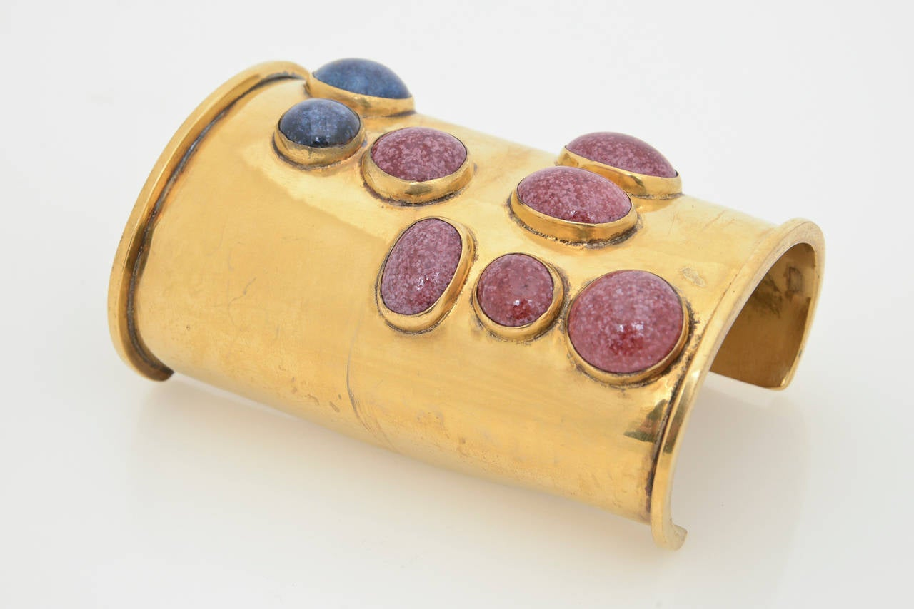 This theatrical and dramatic wide vintage Mary McFadden wide cuff has lapis and another stone against the gold. It is signed Mary McFadden Hand Crafted. It envelopes a time of Egyptian revival meets modern. This needs a long arm and a woman who is