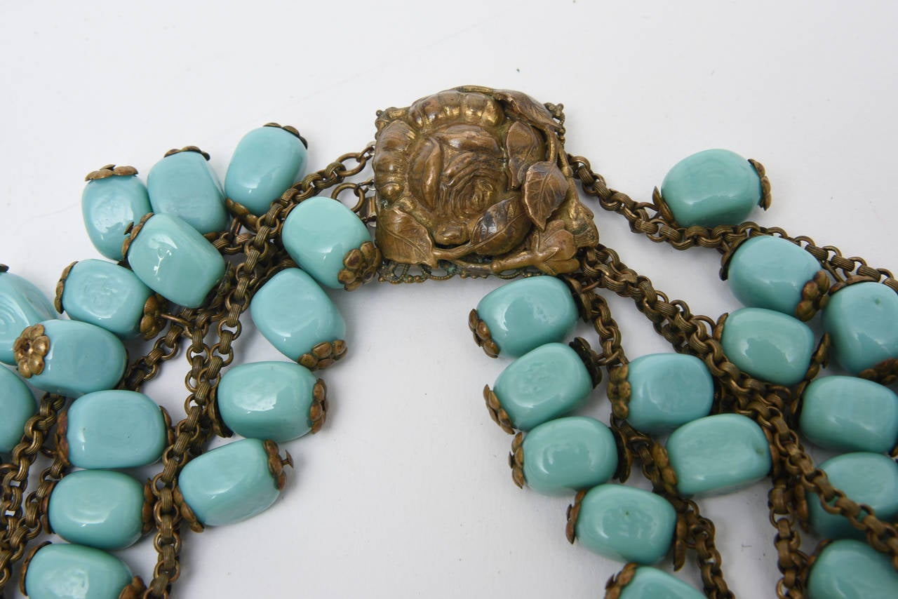 This stunning and dramatic vintage four strand bib necklace by Miriam Haskell is an early work that is unsigned. The gilt metal that makes up small links holds the luscious turquoise glass beads together with a flower design on either side of the