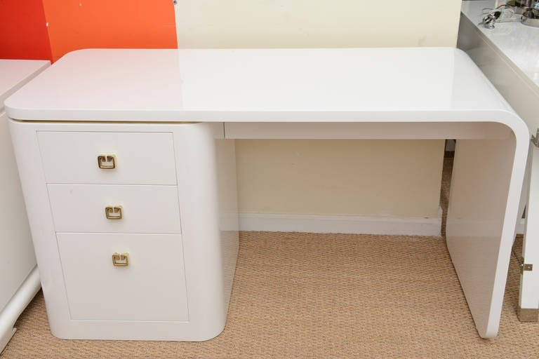 desk used as vanity. This fantastic white lacquered with three pull out drawers original  polished brass hardware has the White Lacquered and Brass Hardware Waterfall Desk or Vanity at 1stdibs