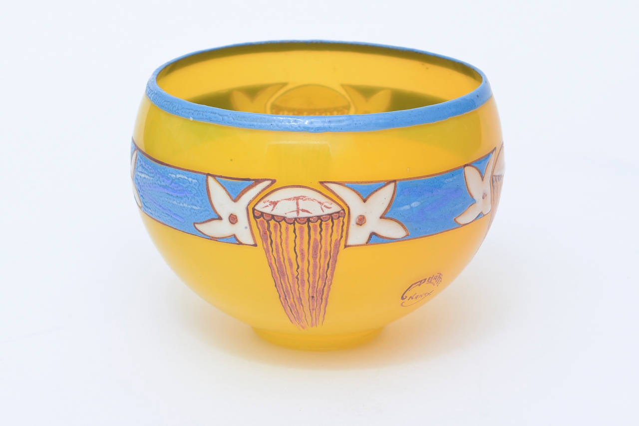 This lovely, small and obscure handblown glass bowl by French artist: Andre Delatte has vivid colors of yellow, sky blue and red to red brown. The artistry of two of the artist's favorite subjects: foliage and hazelnuts is repeated in his oeuvre of