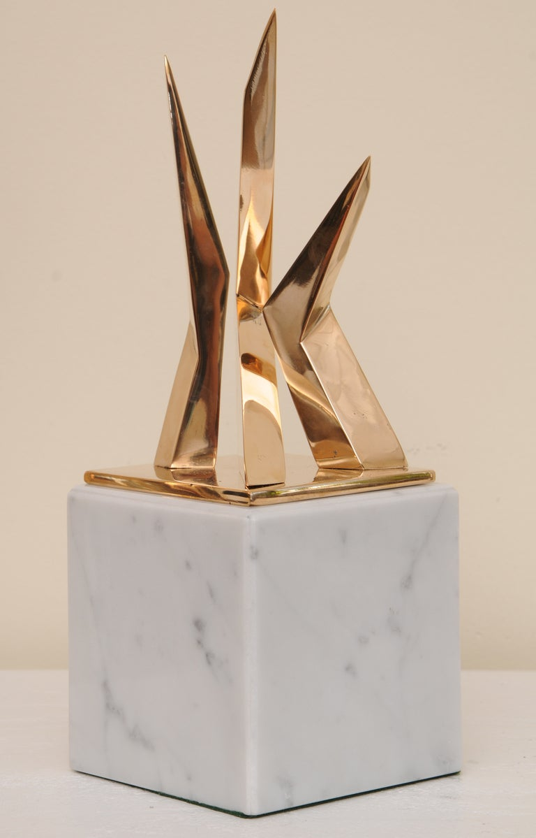 The intersecting sculptural lines of this French signed bronze sculpture by Boucher is polished and has a rose gold color. It sits on a Carrara marble block base, that is not attached. The measurements for the sculpture alone are as follows: 9