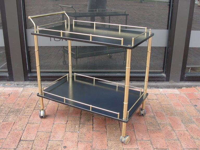 Two-tier and brass faux bamboo rolling bar cart.