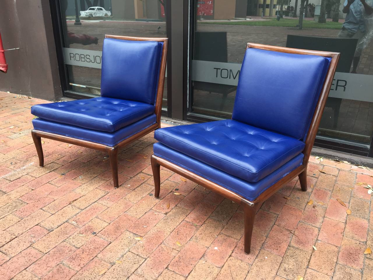 Classic pair of slipper chairs designed by T.H. Robsjohn-Gibbings, circa 1954. The frames are walnut and the chairs have been recently reupholstered in button tufted soft Yves Klein blue leather. To die for!