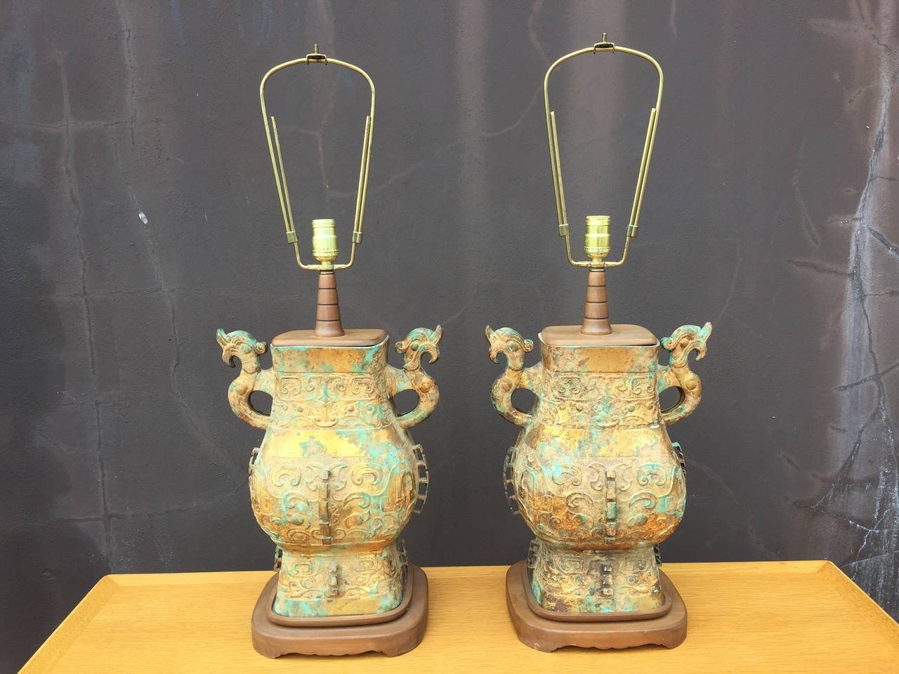 Intricate details and a wonderful verdigris camouflage pattern on brass bases. Body of lamp is 20.25 inches tall.