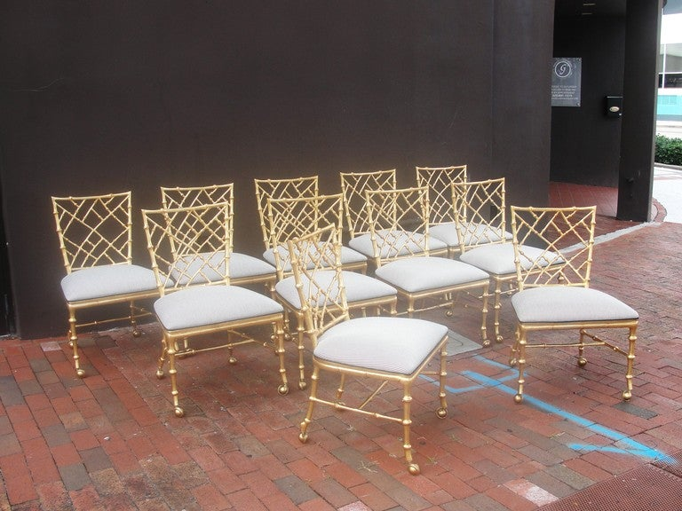 Very hard to find in this quantity - these magnificent Gold gilded aluminum side chairs on casters - are designed by Phyllis Morris. Exaggerated faux bamboo detailing with tapered legs, upholstered in black and white stripes.  Because of the