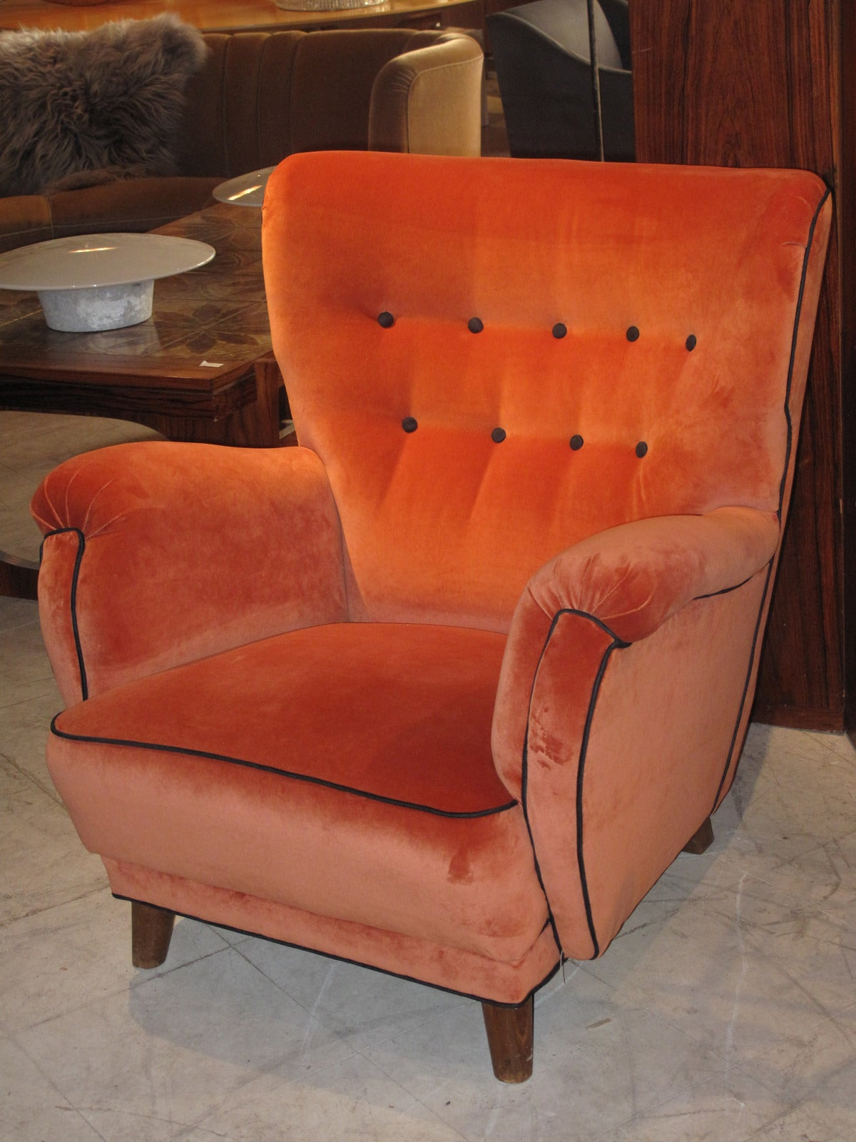 Danish 1940s large-scale club chair upholstered in orange velvet with black trim and button accents.
