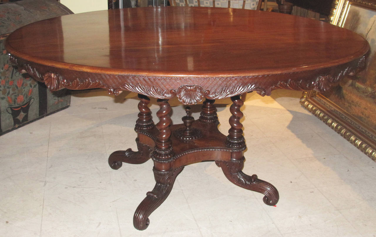 A good quality Danish 19th century mahogany centre table; circa 1850s. The molded edge top over a shaped cross-hatched carved apron with foliate borders intersected with scallop shells. The top on four barley twist supports on a quadripartite