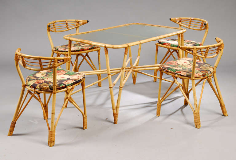 "Dining table with frosted glass top and 4 dining chairs in sturdy rattan, from 1940's Denmark, very well constructed. Flowered cushions for chairs. Table measures 28"" high X 28"" wide X 43"" long"