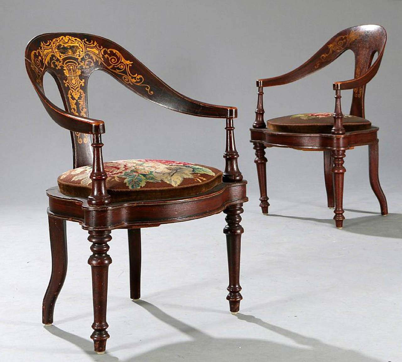 A pair of Danish mid-19th century spoon back chairs. The back splats and arms with painted decoration. The arms ending in turned front supports on molded and shaped needle-point upholstered seats raised on front turned legs and out-curved back legs.
