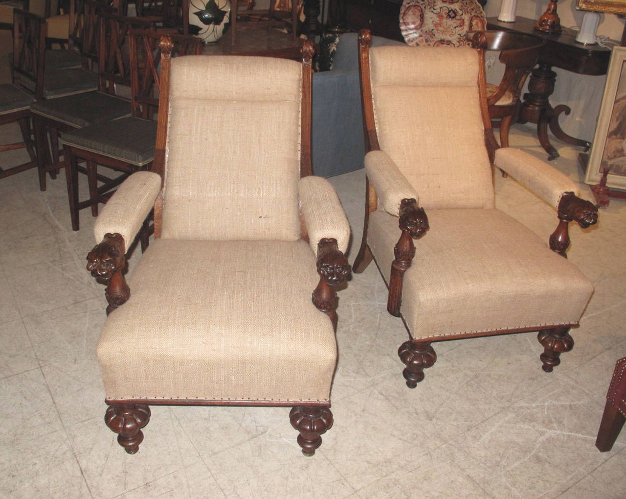Pair of slope-back late 19th century oak library armchairs with arms terminating in lion head carvings. The chairs upholstered in a burlap fabric.