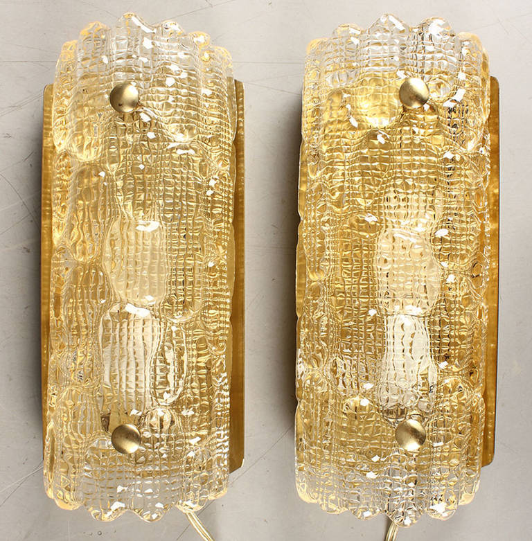 Pair of gold glass textured glass wall sconces by Carl Fagerlund for Orrefors of Sweden, circa 1950s-early 1960s. The brass-mounted textured glass on brass backplates. Note: We have several pairs. Also several pairs of clear glass sconces.