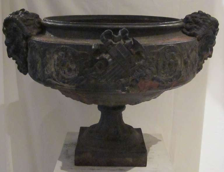 19th century French weathered bronze urn with head of pan on the sides and decorative relief on the body of the urn.