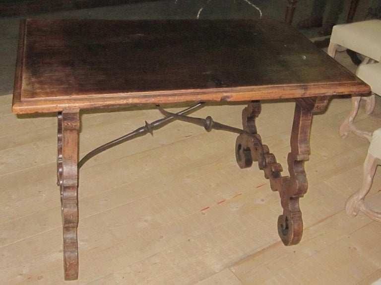 19th century Italian walnut fratino tavolo side table with iron cross bar base. Beautifully carved leg detail.