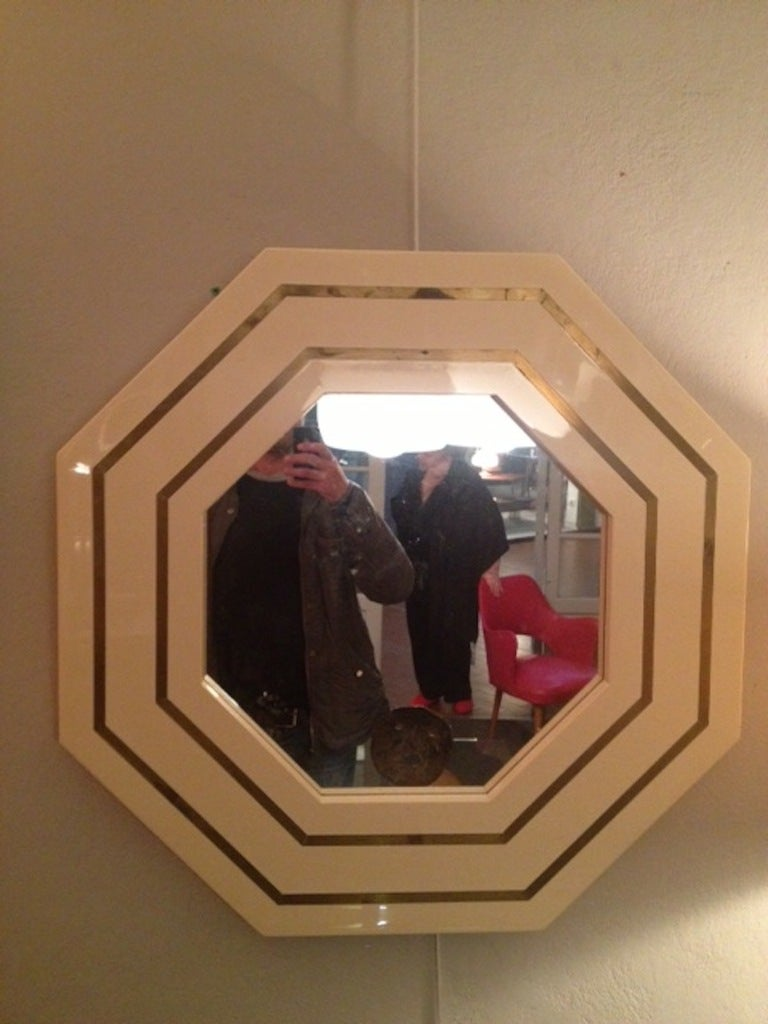 1970s French octagonal cream plexiglass mirror with brass inlay.
