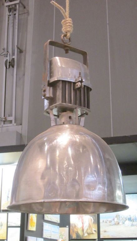 1940s pair of Industrial aluminum light fixtures from a factory in France.