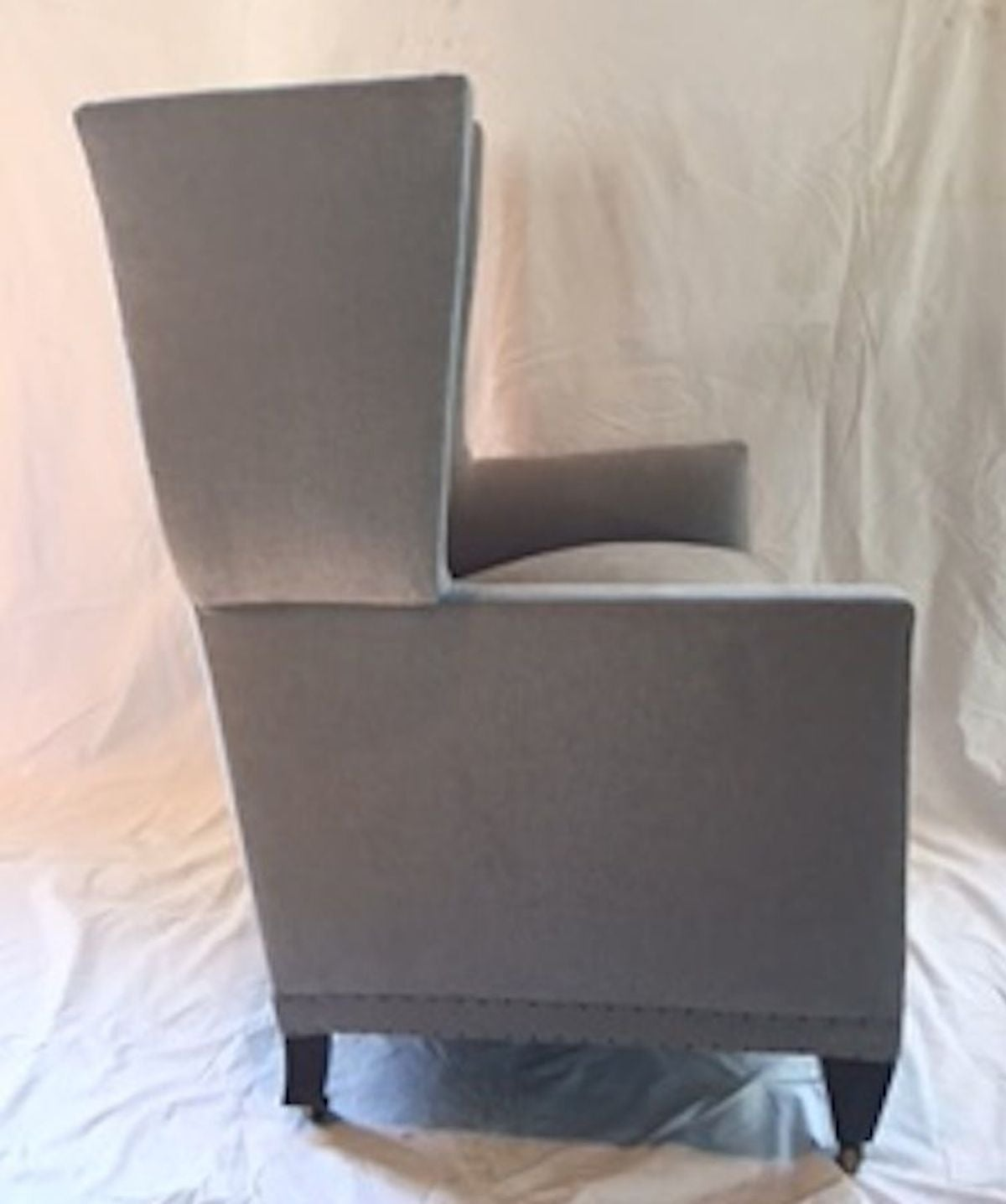 English style pair of upholstered grey wing back armchairs with a high back.