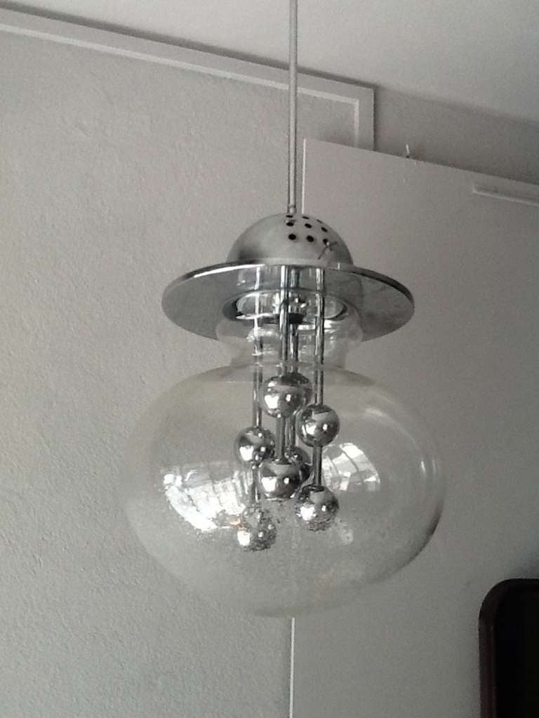 Clear glass globe chandelier appears as if there are water droplets at the bottom of the light fixture. Multi chrome balls are centred within the glass globe.