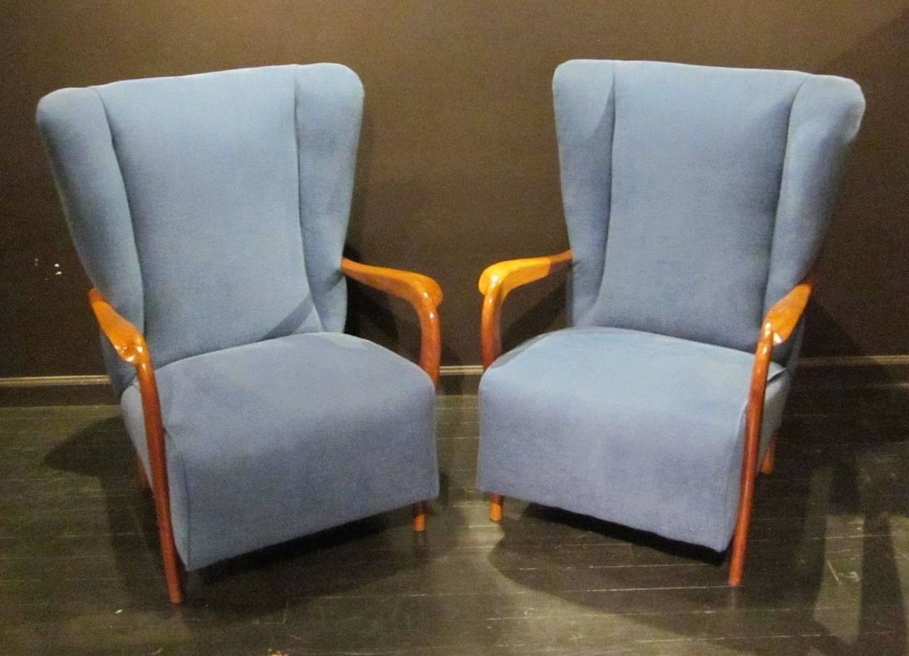 Curved wooden arms and high backs accent this pair of Mid-Century Italian chairs. The shaped wooden arms are very interesting as they curve downward to form the front legs of the chairs.