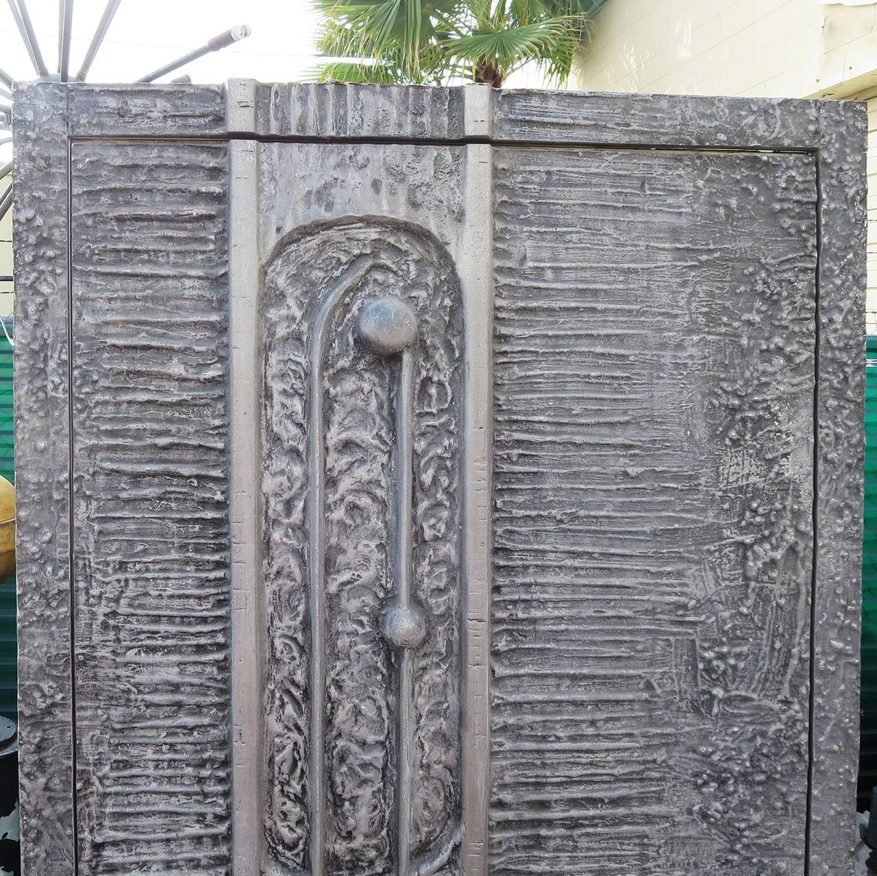 """Best known for the """"Heroic Sunset"""" doors for Forms + Surfaces, McCarroll and Gillespie created another masterpiece of design with this unique sculptural door. The design of the door surface is integrated into the surrounding frame of cast aluminum."""