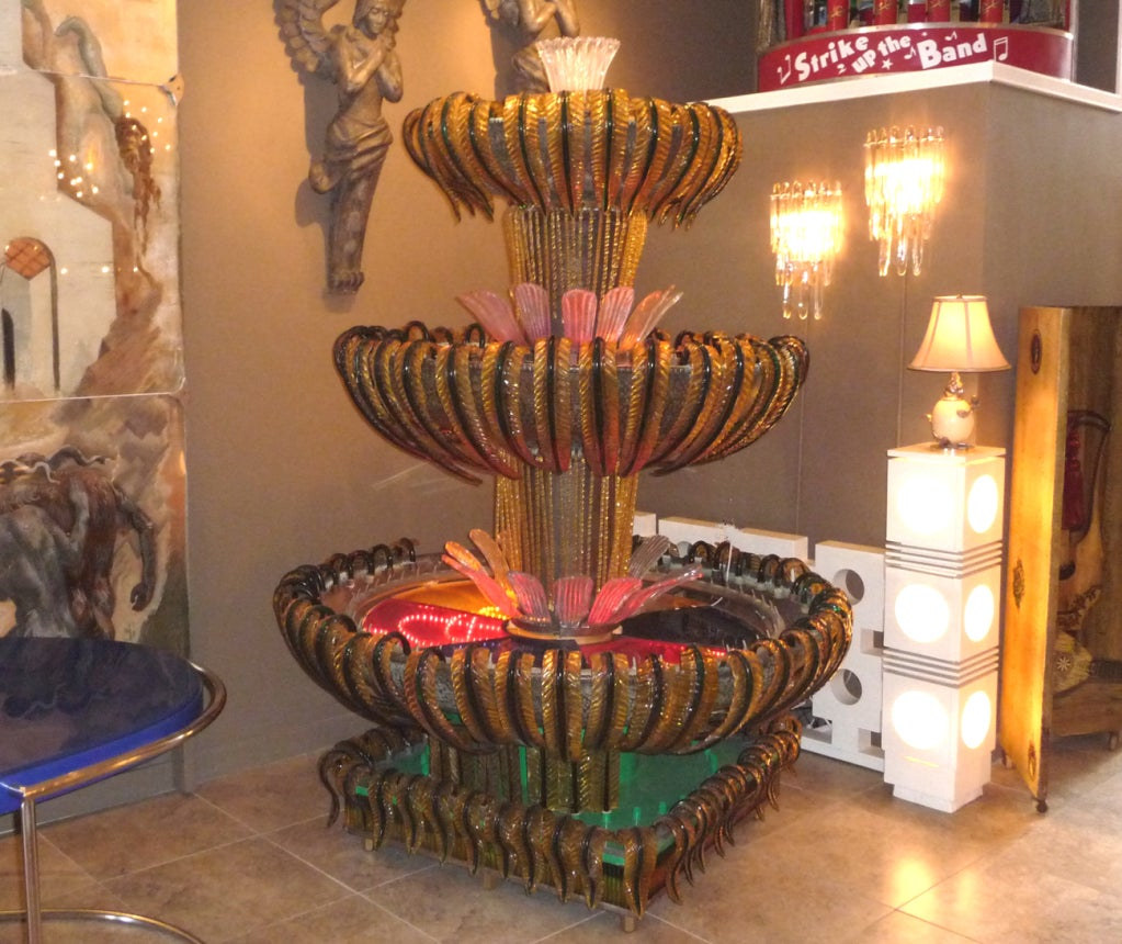 "This an absolute show stopper! Multiple ""leaves"" of hand molded Italian Murano glass surround each tier of the free standing fountain. Each fountain bowl is made of formed copper, built around a central column, decorated with curled stems of"