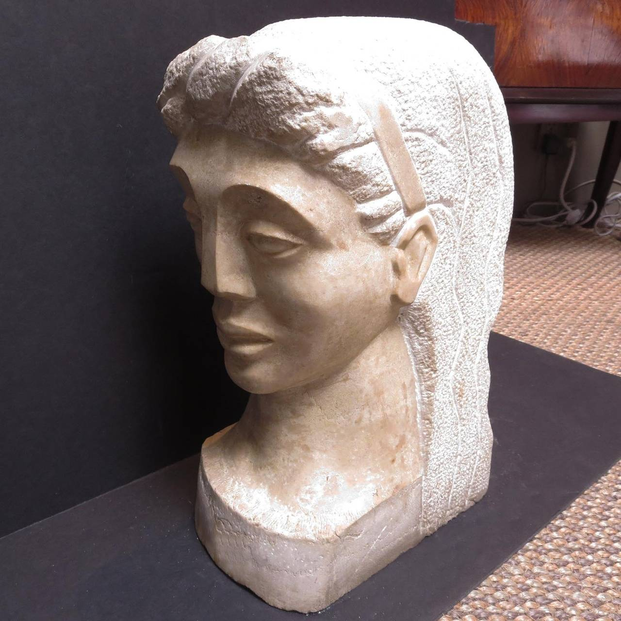 A strong and stylized bust of a woman from the 1930's, signed by an artist MT. The head is solid marble, with a smoothly polished face, and textured hair. The sculptured carving is of the highest quality, reminiscent of the Hollywood Bowl Art Deco