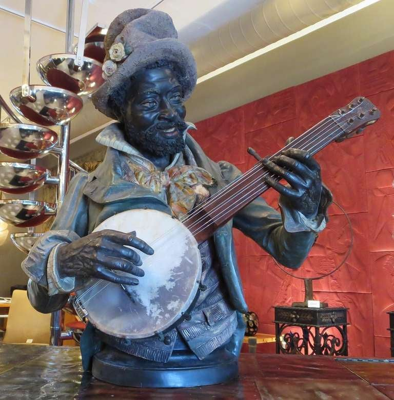 Created by Goldscheider of Vienna around 1900, this figure has been seen in reproduction bronze forms. Ours is the original ceramic, in original polychrome painted finish. The figure shows beautifully, with only minor surface wear. The banjo has