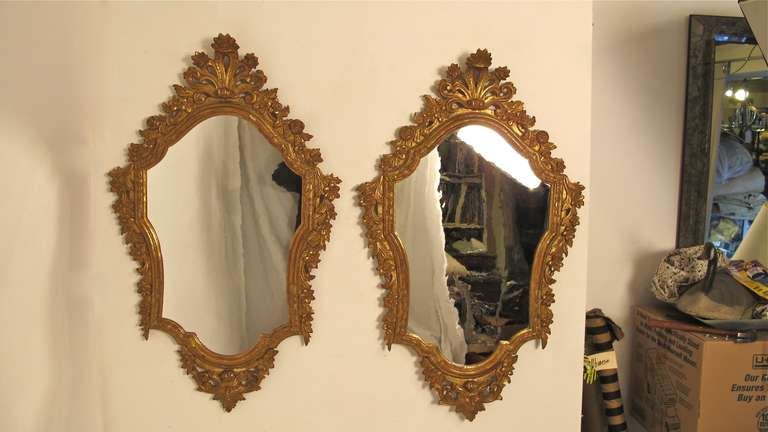 An exceptional matched pair of hand carved and gilded Italian mirrors. Highly carved with flowers and swags, with original glass (possibly re-silvered) and original wood backs. Italy, late 18th century.
