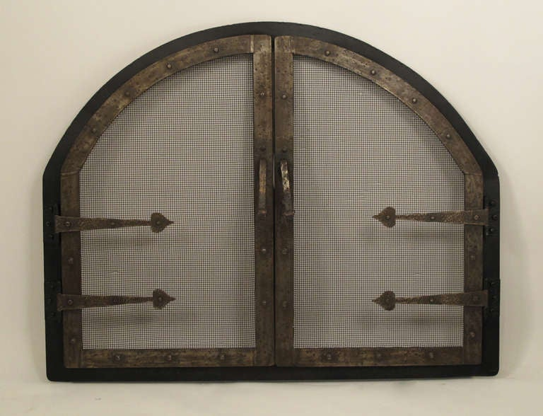 A handsome Arts and Crafts custom made wrought iron fire screen insert. Additional dimensions are: The interior opening is 32 inches x 26 inches. The front vertical side pieces measure 16 inches from the floor to the beginning of the upper arch on
